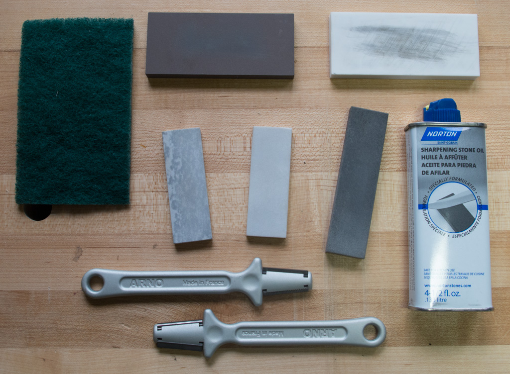 Oilstones and oil (center), ceramic stones (top, with a Scotch-Brite pad top left for cleaning), and carbide sharpeners (bottom) for sharpening knives.