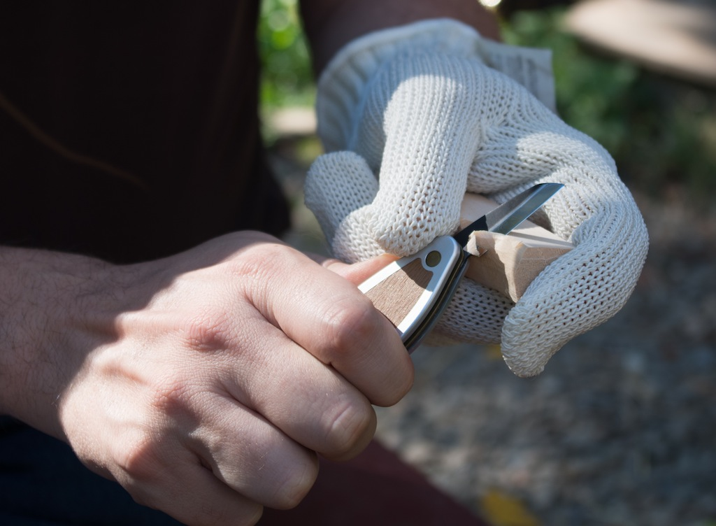 Pushing the knife with the thumb of the hand holding the wood.