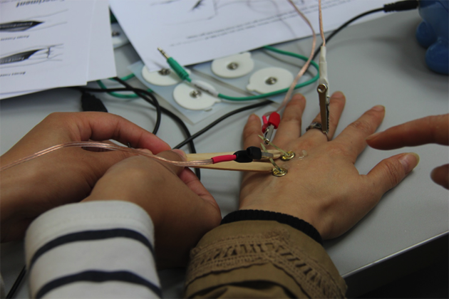 Staff of Zhejiang Science and Technology Museum use electrodes placed on the surface of their skin and connected to a SpikerBox, an inexpensive open source device used to amplify and measure the rates of action potentials traveling through neurons